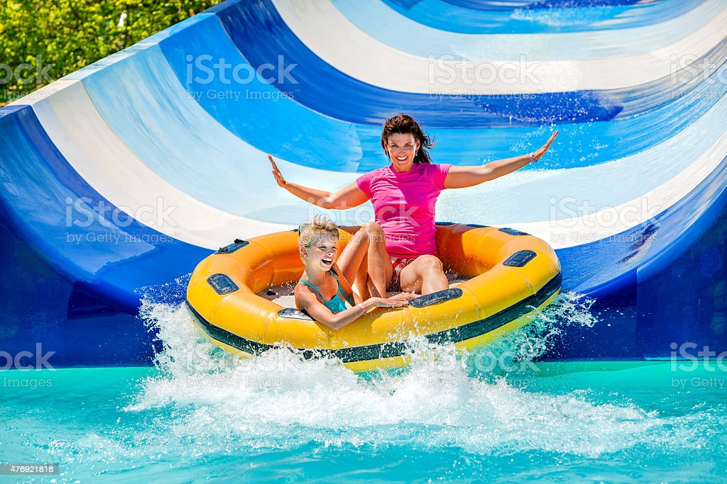 Child with mother on water slide at aquapark stock photo