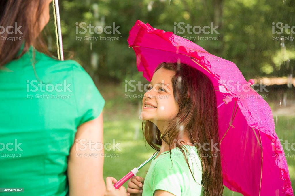 Child with pink umbrella looks up at mom in rain. stock photo