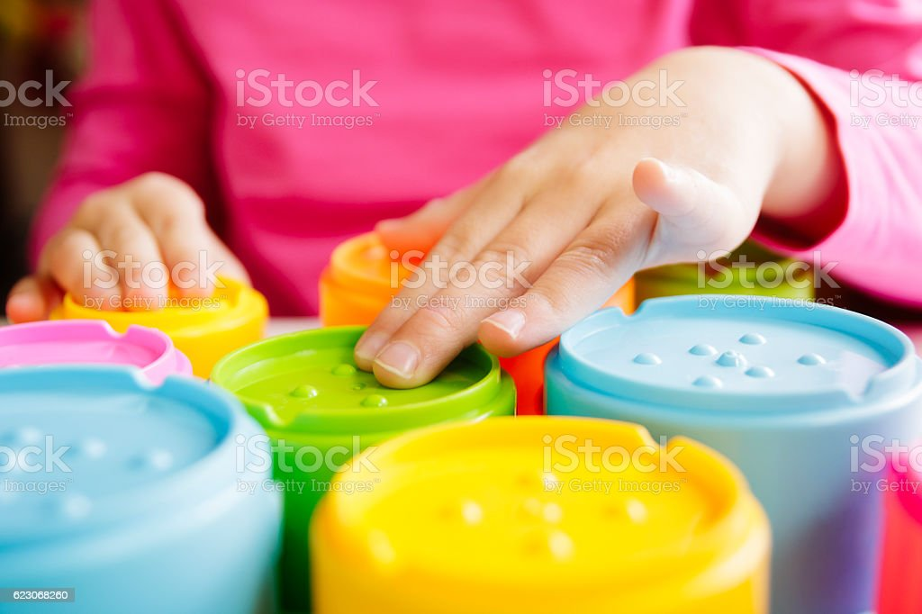 Child with poor vision playing and touching the tactile toys stock photo