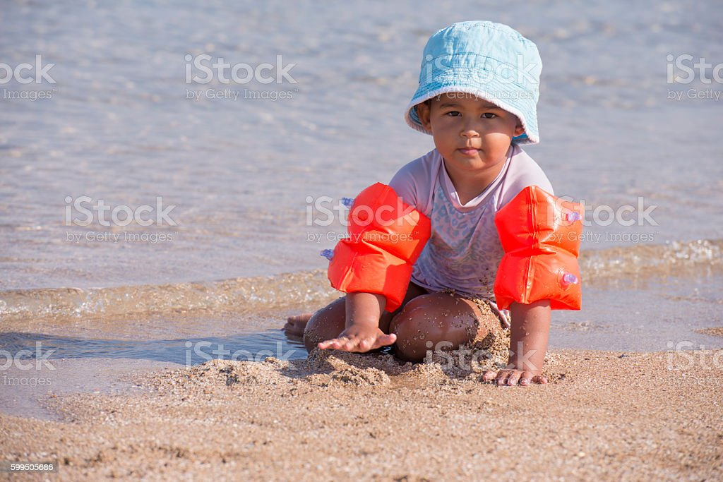 Child with safety inflatable  water wings on Beach. stock photo