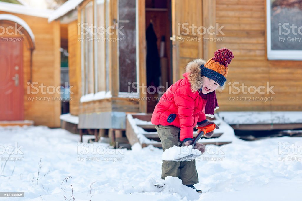 Child with shovel in winter stock photo