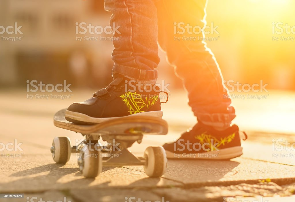 Child with skateboard on the street at sunset light. stock photo