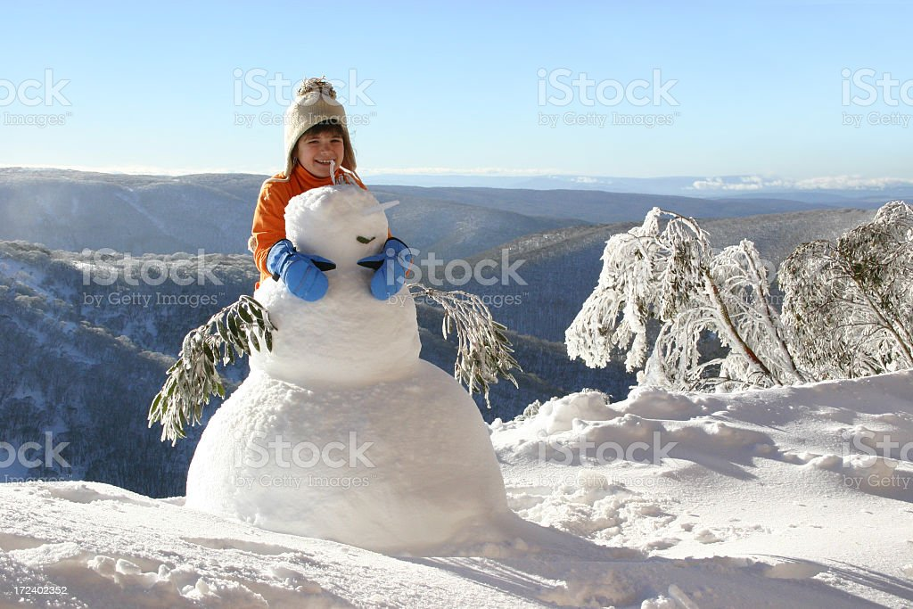 Child with snowman stock photo