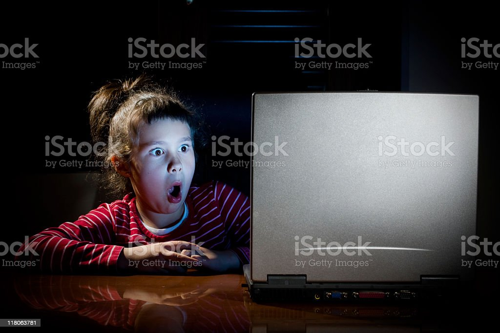 Child with surprised face in front of laptop. stock photo