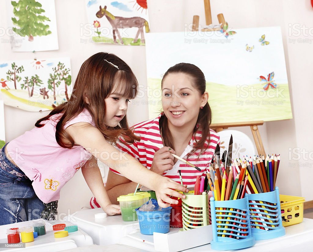 Child with teacher draw paints in play room. royalty-free stock photo