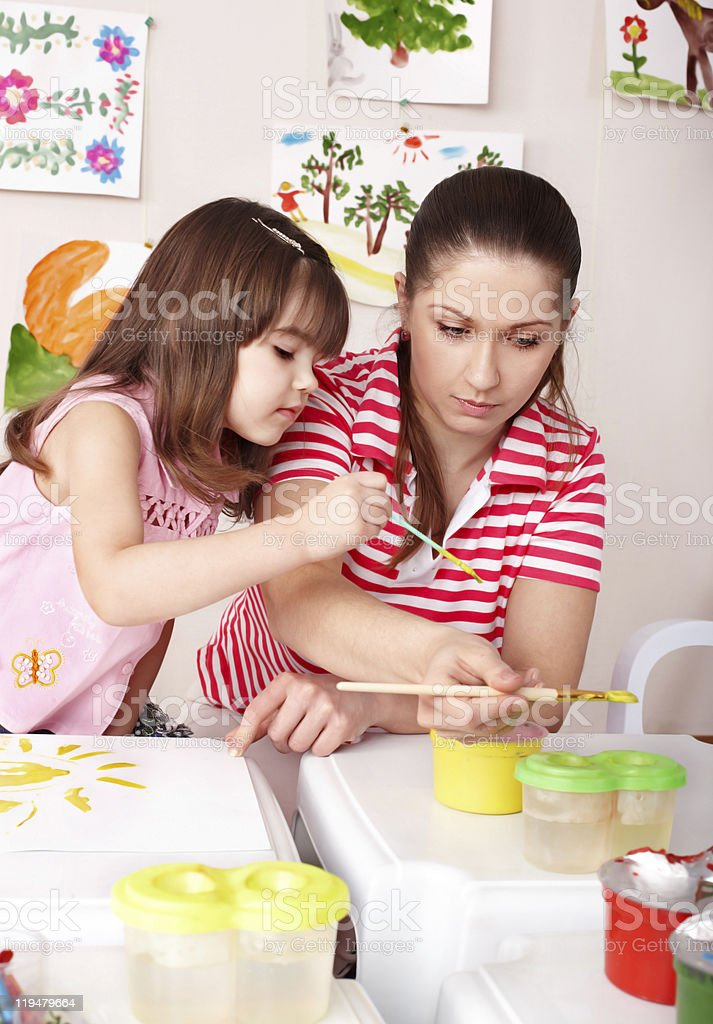 Child with teacher draw paints in preschool. royalty-free stock photo