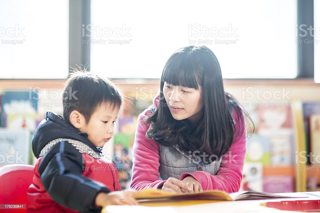 child with teacher in classroom royalty-free stock photo