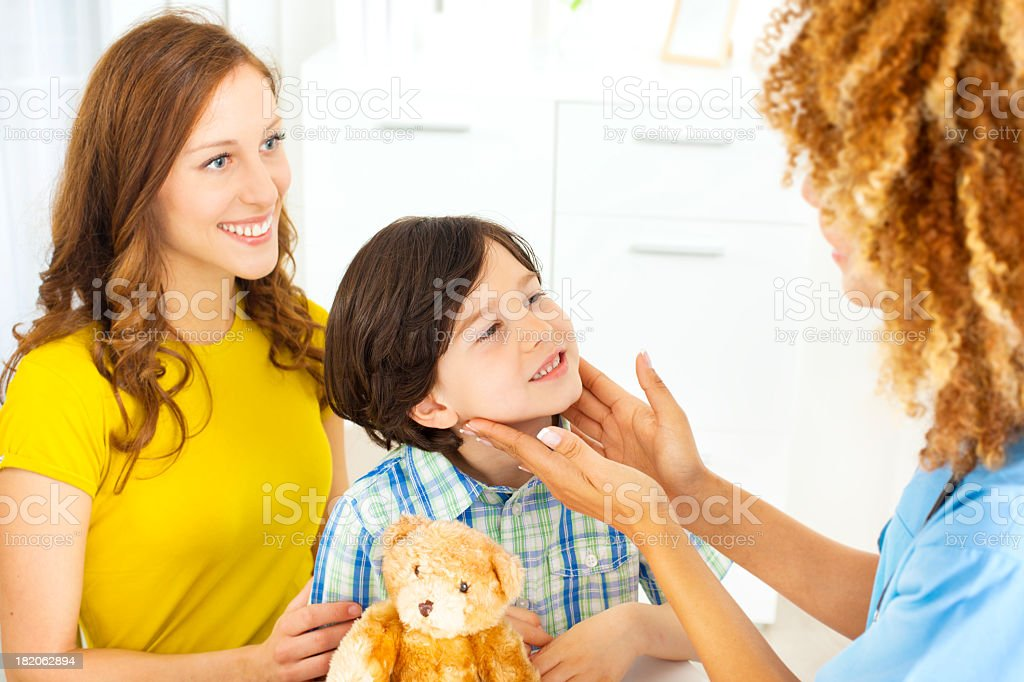 Child with teddy bear at doctors office. stock photo