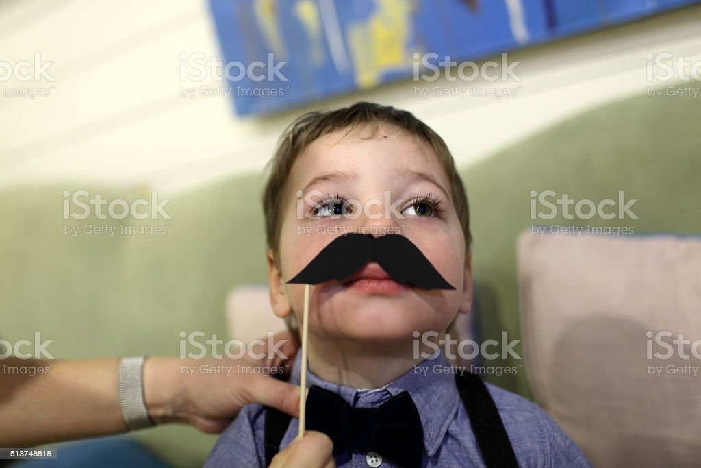 Child with toy moustache stock photo