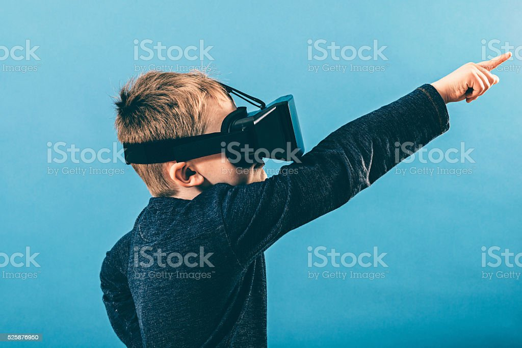 Child with VR glasses points hand out in the air stock photo
