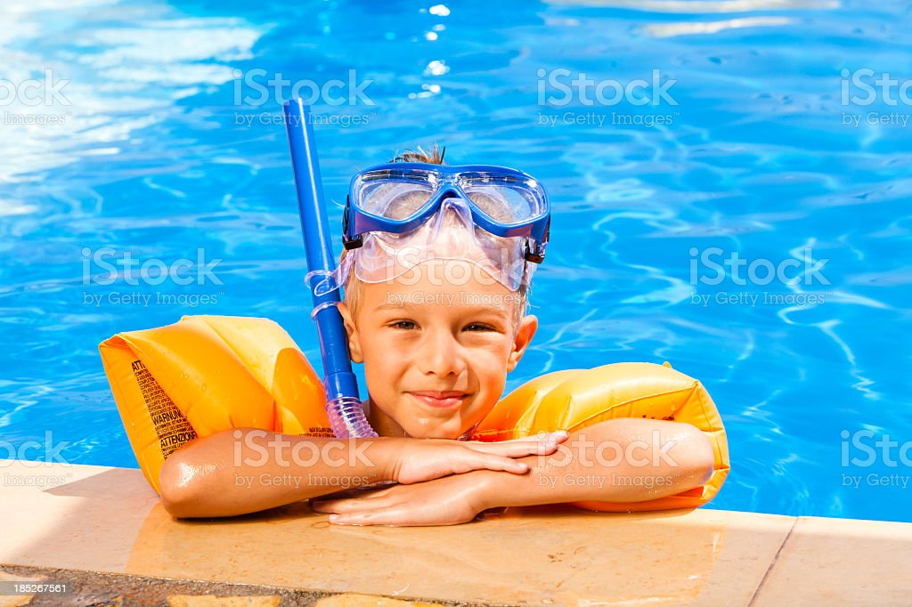 Child with water wings relaxing the swimming pool stock photo