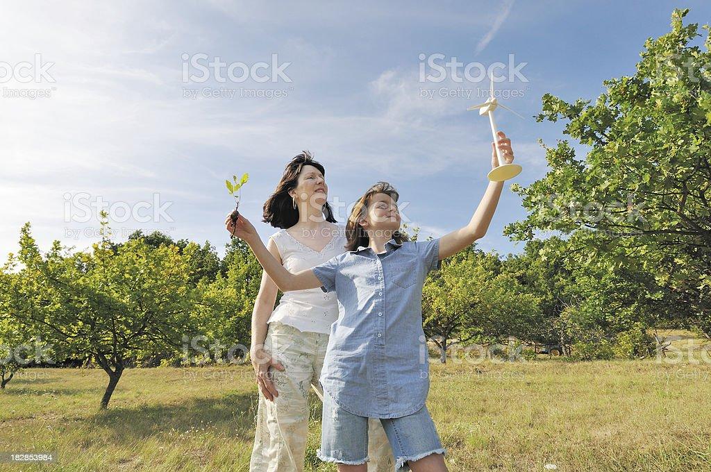 child with wind turbine and oak sapling royalty-free stock photo