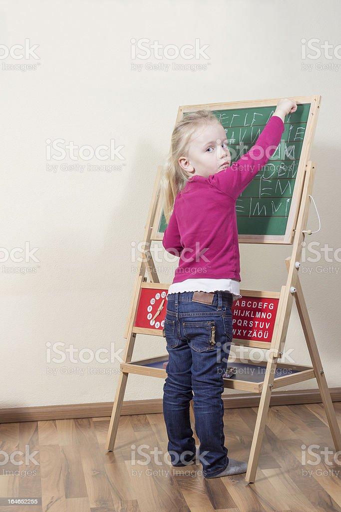 Child writes on the blackboard. royalty-free stock photo