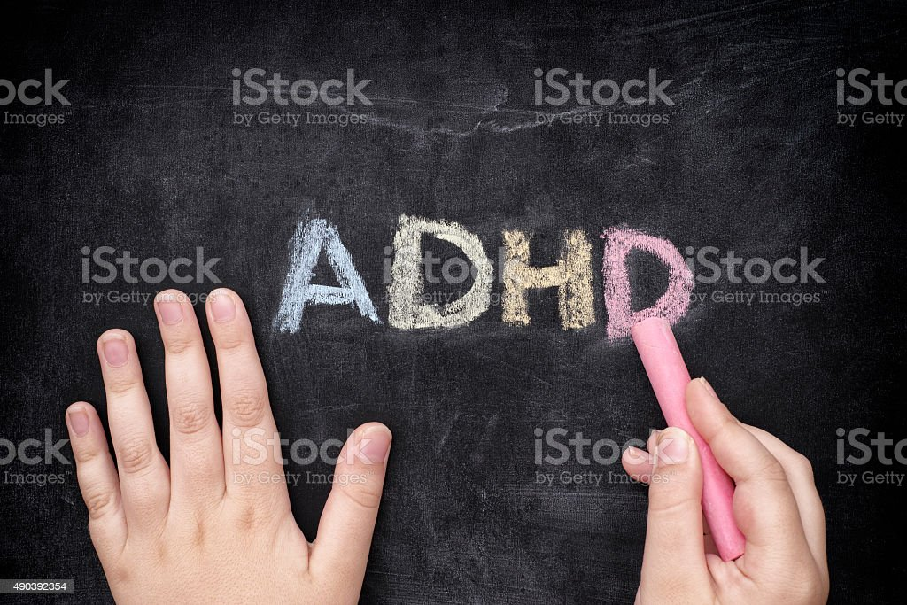 Child writing ADHD on blackboard stock photo
