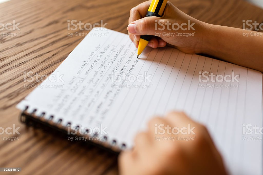 Child writing by hand on notepad stock photo