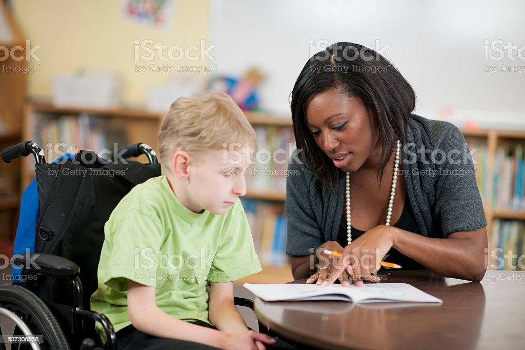 Child Writing in Class stock photo