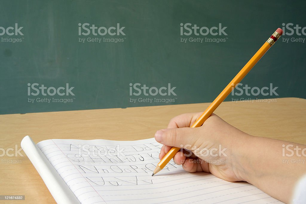 Child writing upper and lower case alphabet on lined paper stock photo