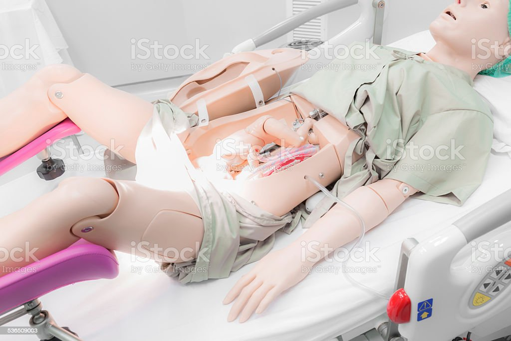 childbirth new born baby from mom's abdomen with medical dummy stock photo