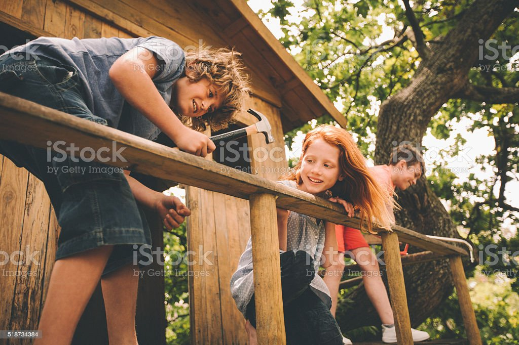 Childhood friends hammering and working to build their treehouse stock photo