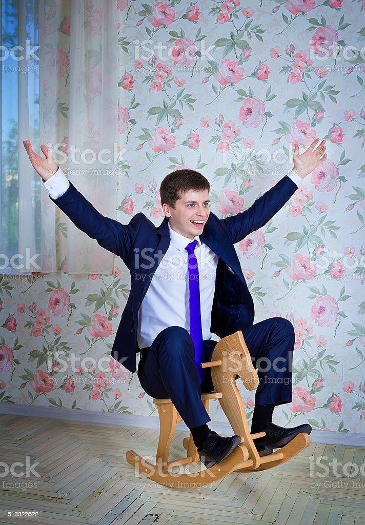 Childish businessman with toy horse stock photo