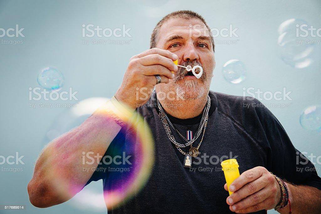 Childish senior man blowing bubbles stock photo