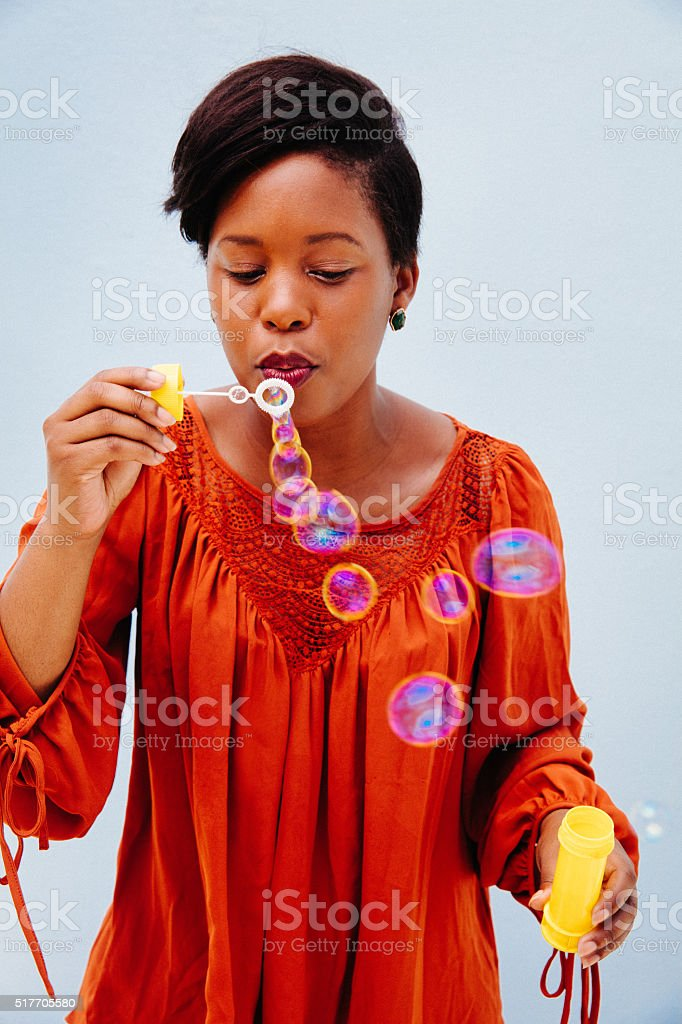 Childish young african woman blowing bubbles stock photo