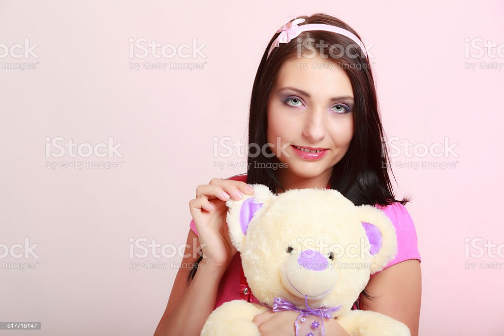 Childish young woman hugging teddy bear toy stock photo