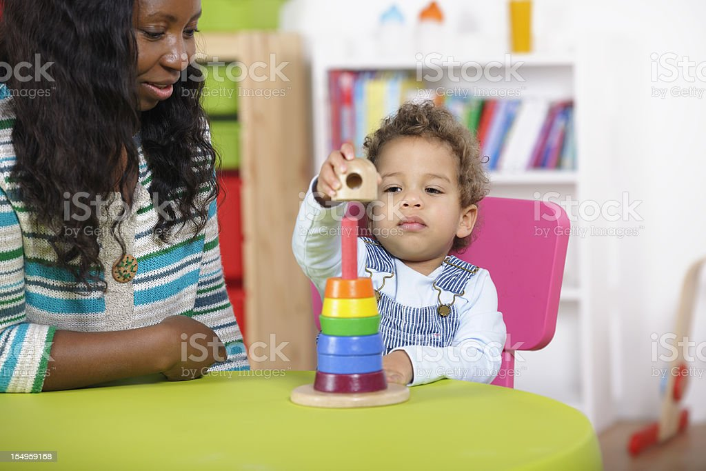 Childminder Supervising Toddler Playing With Developmental Wooden Toy. stock photo
