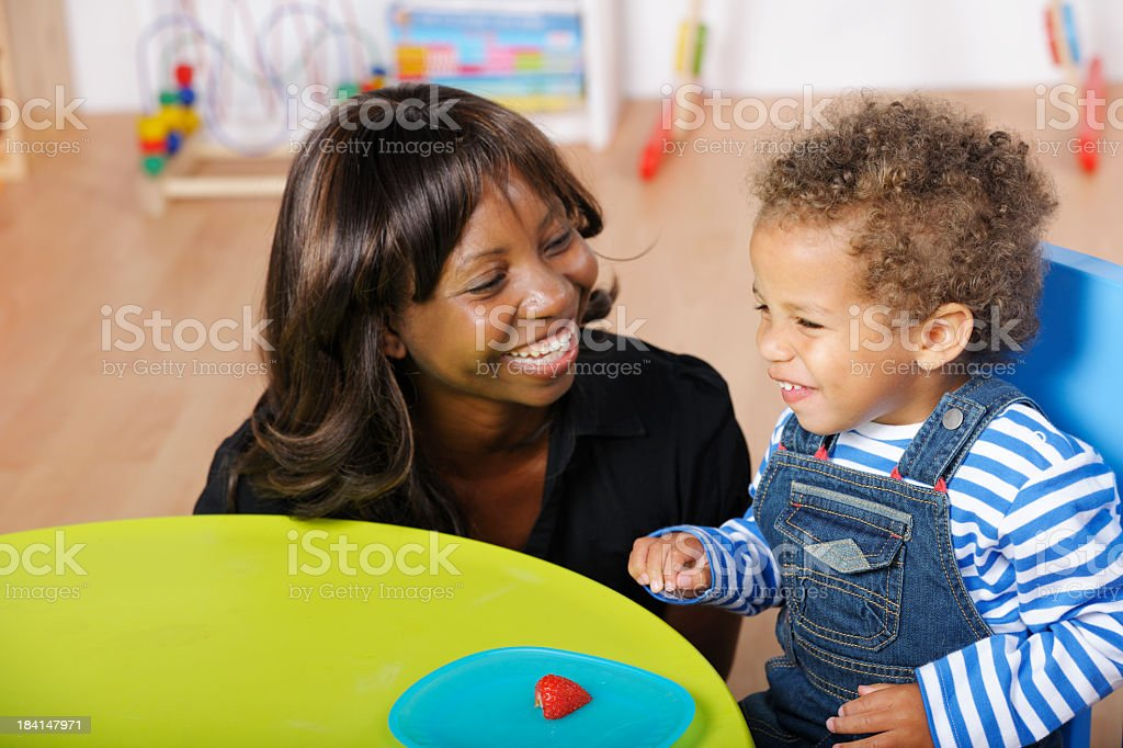 Childminder/Carer/ And Toddler Enjoying A Happy Moment During Mealtime royalty-free stock photo