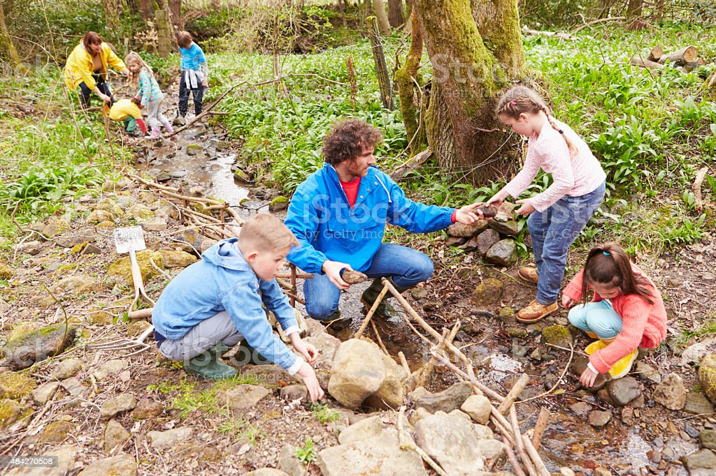 Children And Adults Carrying Out Conservation Work On Stream stock photo