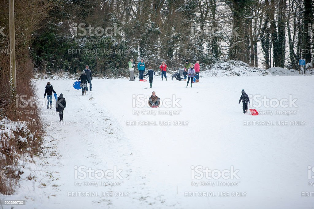 Children and adults enjoying a days tobogganing stock photo