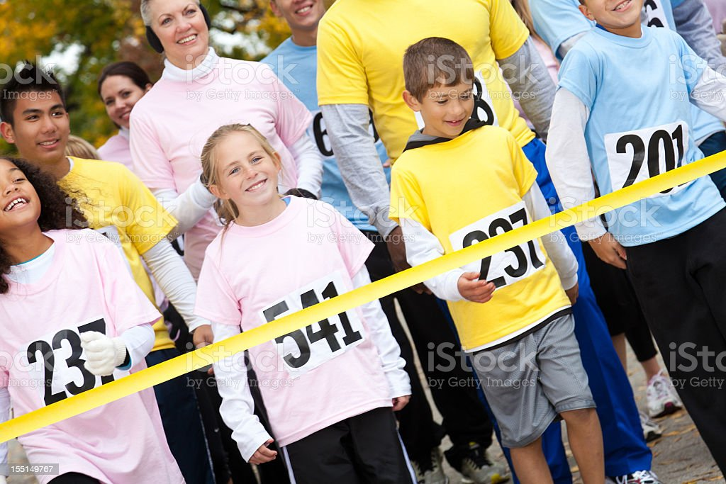Children and adults happily crossing a race finish line royalty-free stock photo