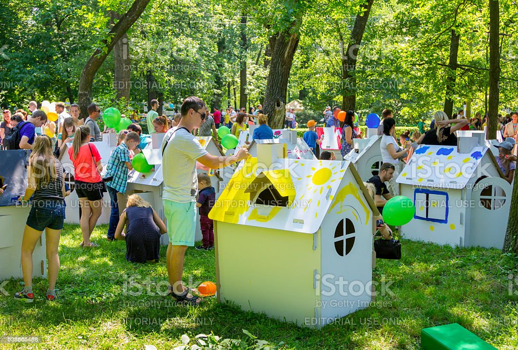 children and adults  participating in painting cardboard houses activity stock photo