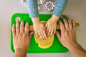 Children and dad hands rolled shortcrust dough