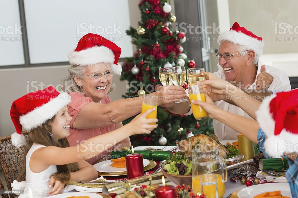Children and grandparents toasting juices during Christmas royalty-free stock photo
