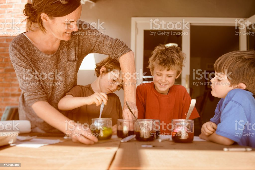 Children and mother dye Easter Eggs stock photo