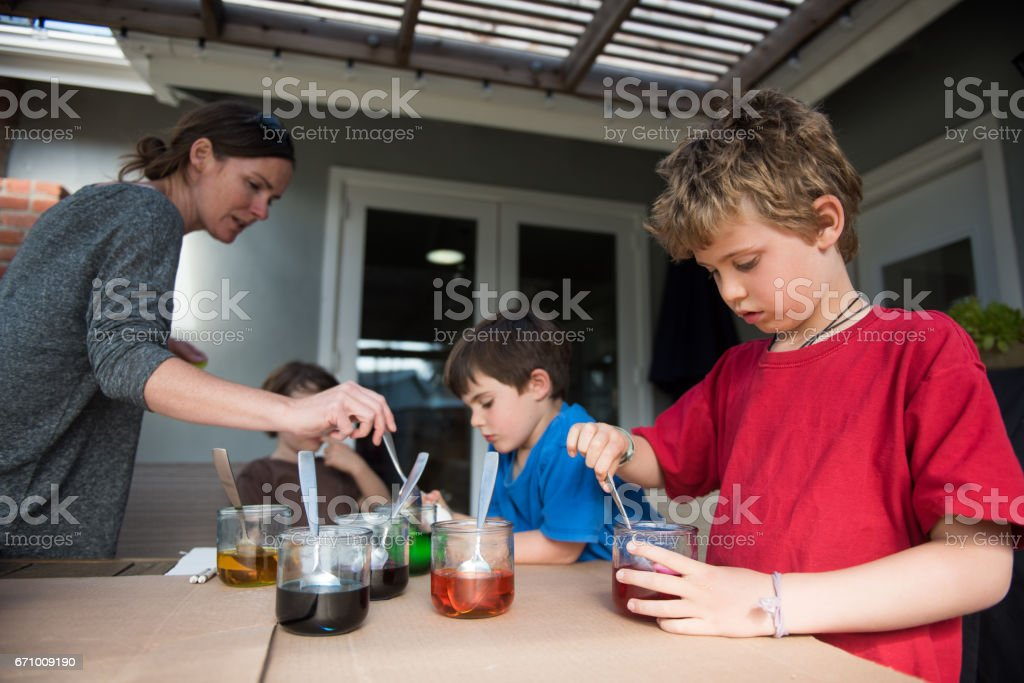 children and mother dying easter egg stock photo