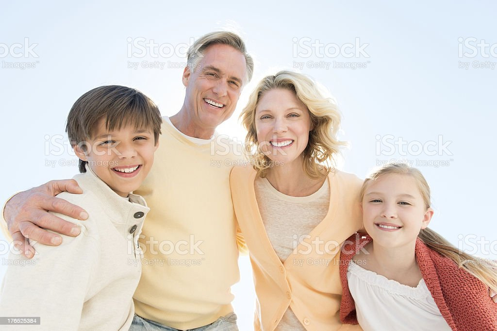 Children And Parents Smiling Against Clear Blue Sky stock photo