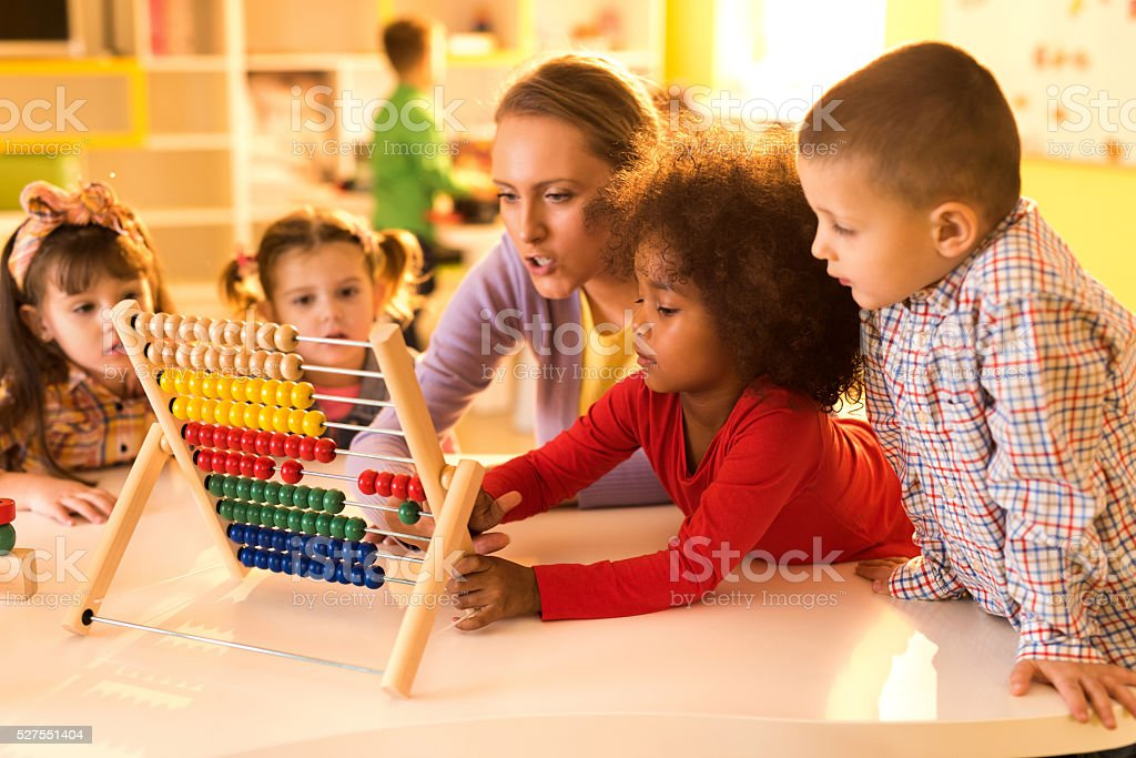 Children and teacher counting with abacus at preschool. stock photo