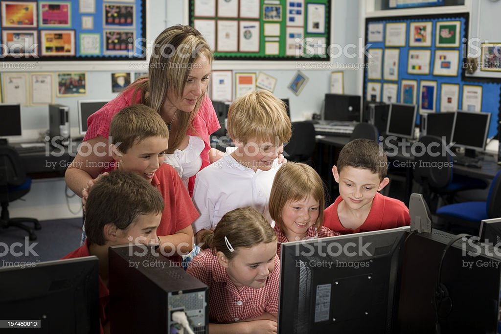 Children and teacher having fun with technology stock photo