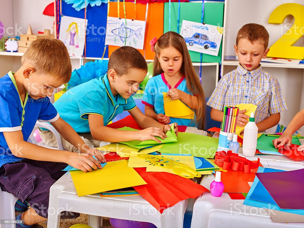Children are making something out of colored paper. stock photo