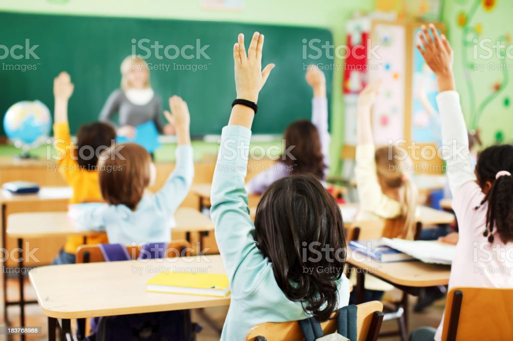 Children are raised hands in classroom. stock photo