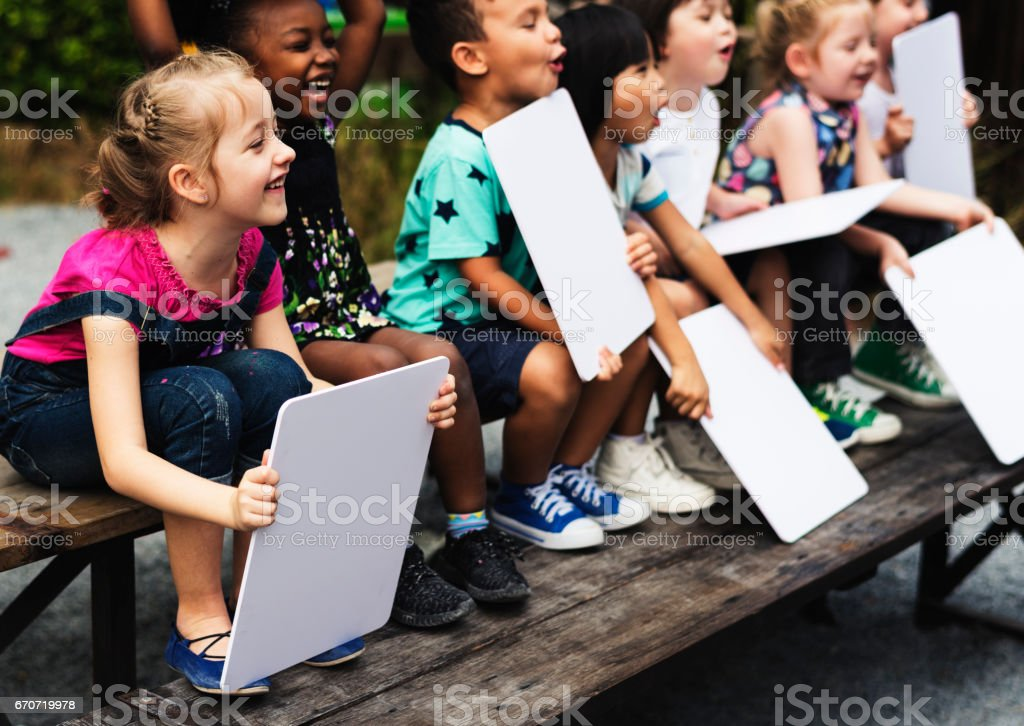 Children are sitting together holding placard stock photo