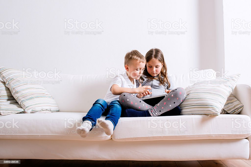Children at home sitting on sofa, playing with tablet stock photo