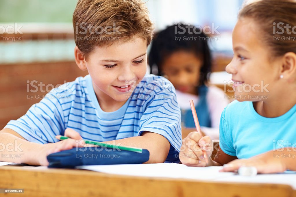 Children at their desks taking notes in class royalty-free stock photo