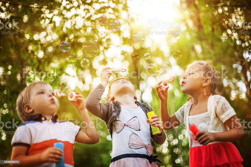 Children blowing bubbles stock photo