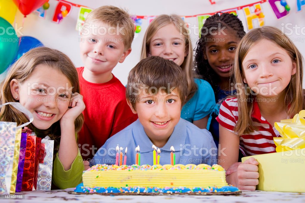 Children Blowing Out Candles on a Birthday Cake royalty-free stock photo