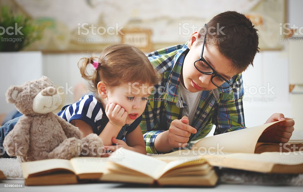 children brother and sister, boy and girl reading a book stock photo
