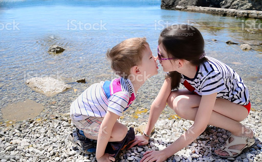 children brother and sister kiss on the beach royalty-free stock photo