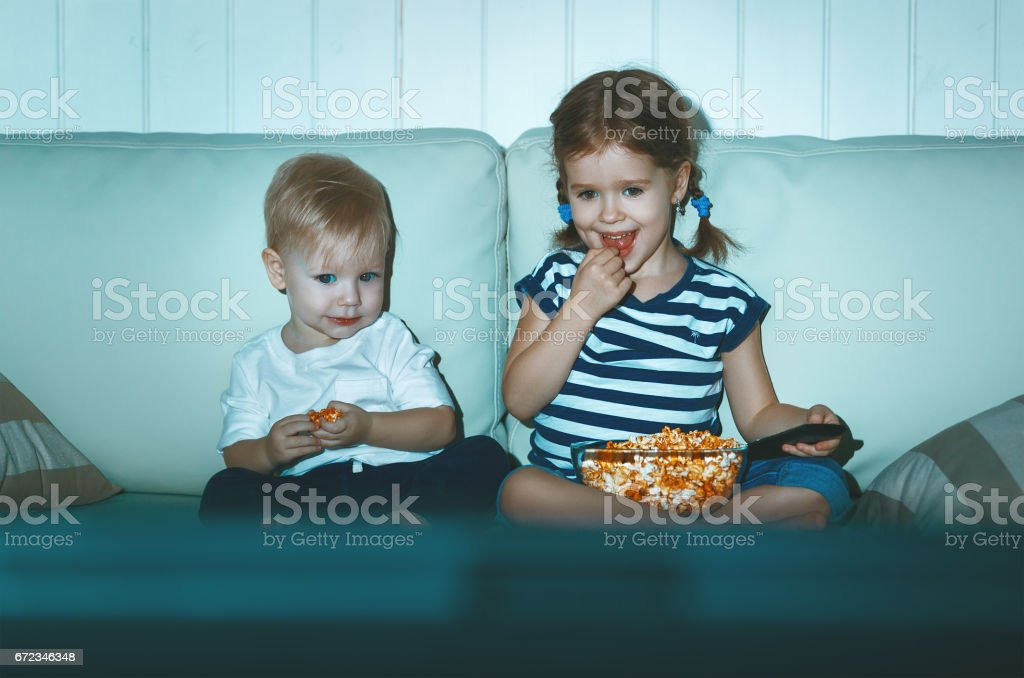 Children brother and sister watching TV in evening stock photo